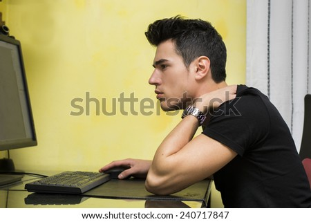 Handsome young man working or studyiing at computer at home or in office, staring at screen with focused expression - stock photo
