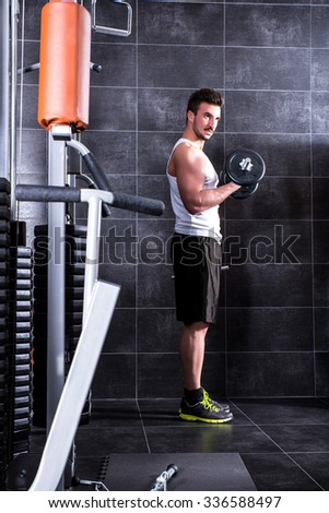 Handsome, young man working out in the gym - stock photo