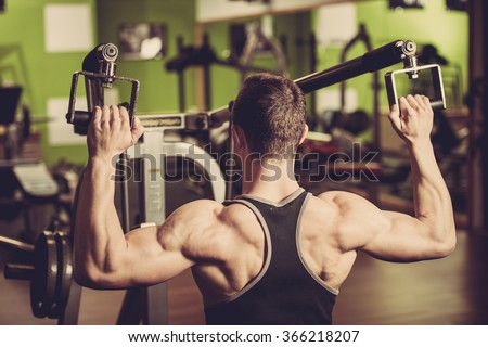 Handsome young man workout in fitness gym - strong mans bodybuilders back - stock photo
