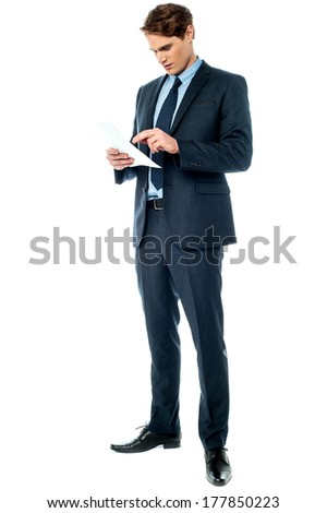 Handsome young manager checking financial report - stock photo