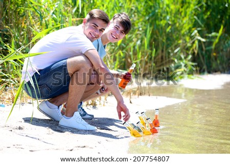 Handsome young men on beach - stock photo