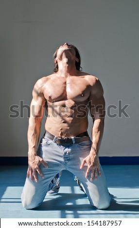 Handsome young muscle man shirtless kneeling on the floor, holding head up, wearing jeans - stock photo