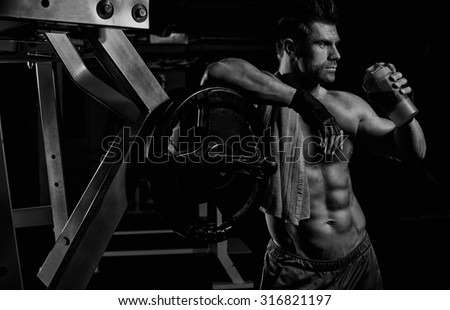 handsome young muscular man drinks a protein in the gym - stock photo