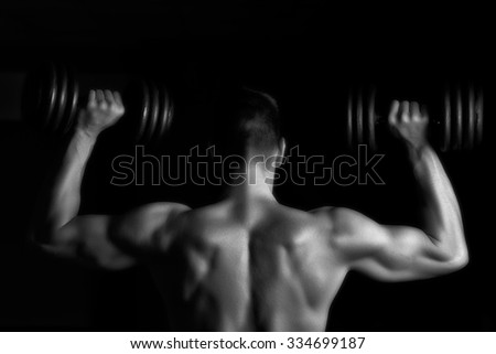 Handsome young muscular man lifting weights over dark background - stock photo