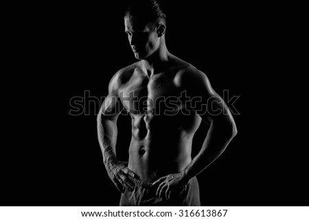 handsome young muscular man posing to the camera - stock photo