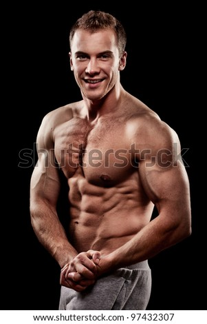 handsome young muscular sports man on balck background - stock photo