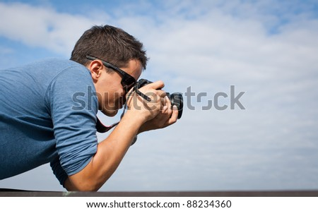 Handsome young professional photographer taking photos against blue sky - stock photo