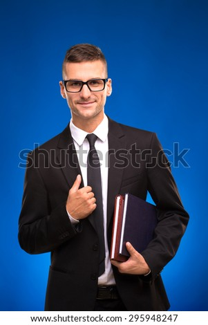 Handsome young scientist smiling on blue. Man with two notebooks keeping his business jacket and smiling. - stock photo
