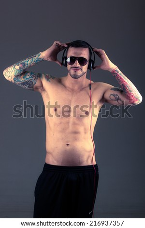 handsome young shirtless tattooed man holding headphones on his head posing - stock photo
