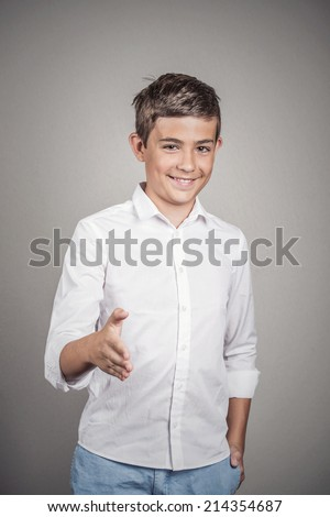 Handsome young smiling man giving extending arm for handshake at camera gesture isolated grey wall background. Positive human emotions, facial expressions, feelings, body language - stock photo