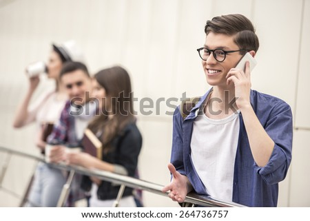 Handsome young student talking on the phone. His classmates in the background. - stock photo