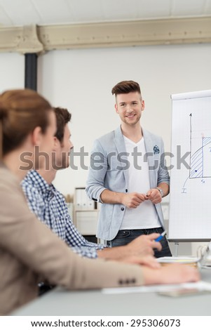Handsome Young Team Leader Discussing to Members Using a Presentation on a Poster While Having a Meeting Inside the Boardroom. - stock photo