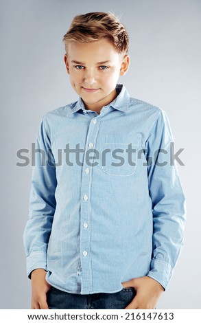 Handsome young teenage boy posing in studio with fashionable hairstyle. - stock photo