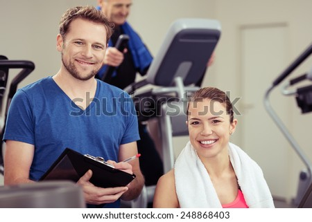 Handsome young trainer with a pretty girl at the gym working out together ion the equipment as he monitors her progress - stock photo