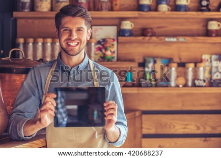 Handsome young waiter in apron is showing a tablet, looking at camera and smiling while standing in the cafe - stock photo
