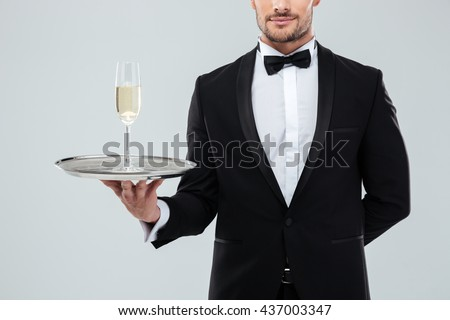 Handsome young waiter in tuxedo and bow tie standing and holding tray with glass of champagne over white background - stock photo