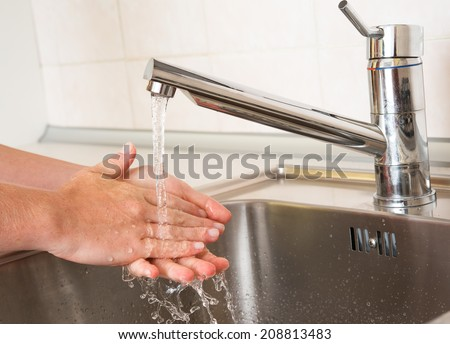 handwashing. woman washing hands under a tap water - stock photo