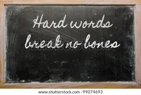handwriting blackboard writings - Hard words break no bones - stock photo