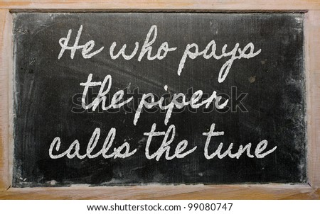 handwriting blackboard writings - He who pays the piper calls the tune - stock photo