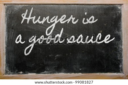 handwriting blackboard writings - Hunger is a good sauce - stock photo