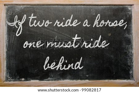 handwriting blackboard writings - If two ride a horse, one must ride behind - stock photo