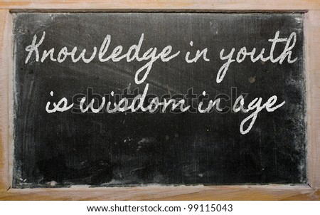 handwriting blackboard writings - Knowledge in youth is wisdom in age - stock photo