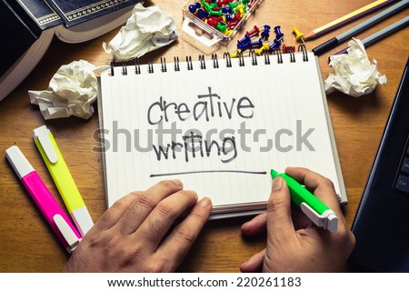 Handwriting of Creative writing word in notebook on the wood table - stock photo