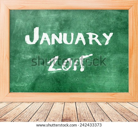 Handwriting text for JANUARY 2015 on green board with wooden paving. - stock photo