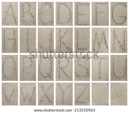 Handwritten alphabet letters on sand background - stock photo