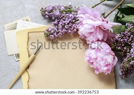 Handwritten letters lilacs and pink peonies on grey background, copy space - stock photo