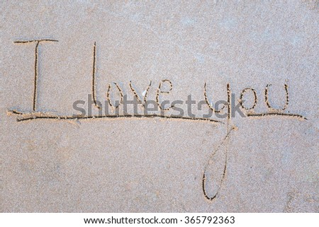 """handwritten of word """"I Love You"""" in sand beach.a - stock photo"""