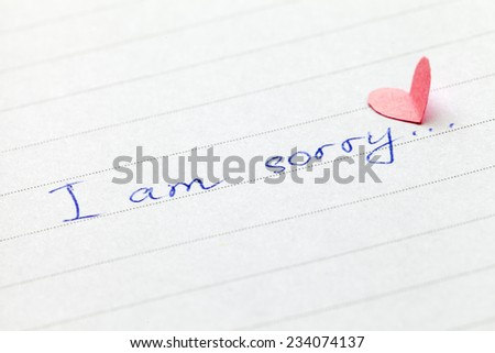 """Handwritten phrase """"I am sorry"""" with heart. Shallow depth of field. - stock photo"""