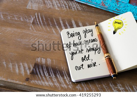 Handwritten text Being gray of hair means you are simply old, not wise with fountain pen on notebook. Concept image with copy space available. - stock photo