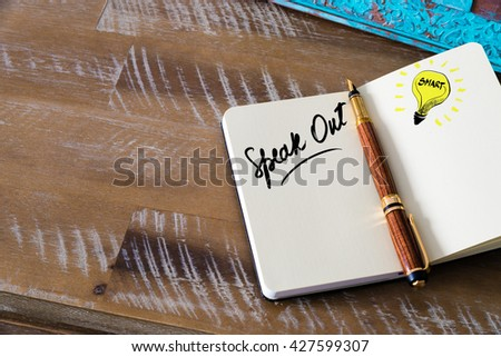Handwritten text Speak Out with fountain pen on notebook. Concept image with copy space available. - stock photo