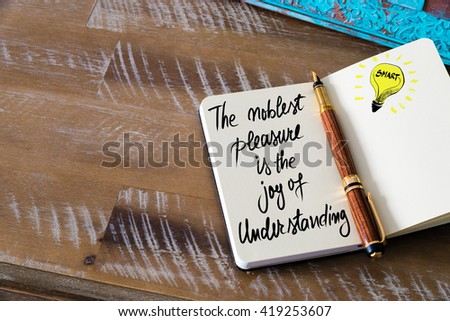 Handwritten text The noblest pleasure is the joy of understanding with fountain pen on notebook. Concept image with copy space available. - stock photo