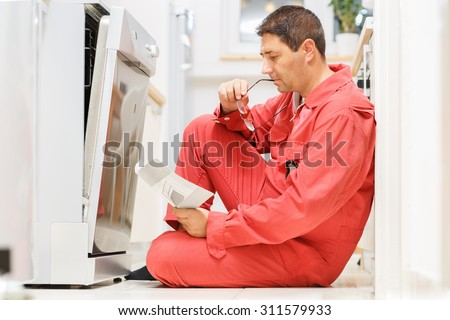 Handy man reading the instruction manual in front of the dishwasher in the kitchen. Copy space - stock photo
