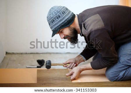 Handy man worker laying parquet in a room - stock photo