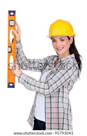 Handy woman holding spirit level - stock photo