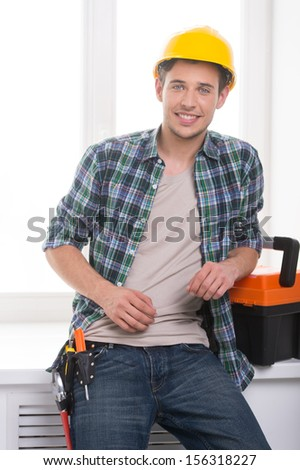Handyman. Cheerful craftsperson looking at camera and leaning at the windowsill - stock photo