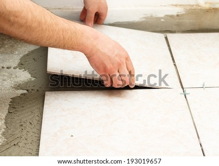 Handyman doing tiling works in kitchen. - stock photo