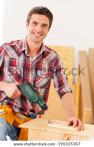 Handyman drilling. Confident young handyman working in workshop and smiling while holding a drill - stock photo