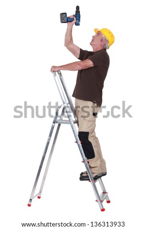 Handyman drilling the ceiling - stock photo
