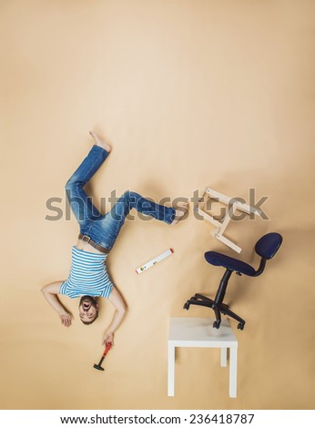 Handyman falling dangerously from a high pile of chairs. Studio shot on a beige background. - stock photo