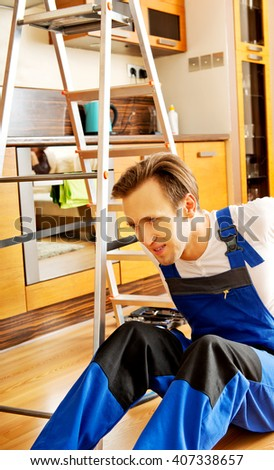 Handyman fell from a ladder and sitting on the floor with backache  - stock photo