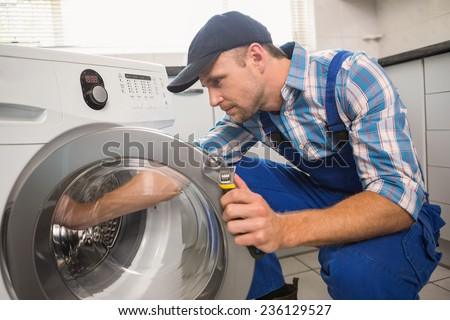 Handyman fixing a washing machine in the kitchen - stock photo