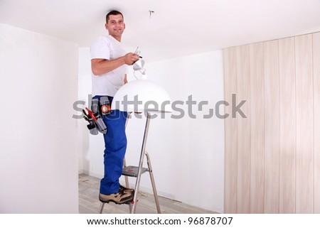 Handyman fixing ceiling light - stock photo