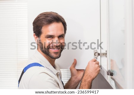 Handyman fixing the cupboard in the kitchen - stock photo