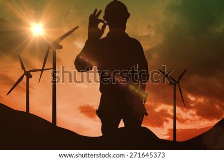 Handyman gesturing okay against sky and mountains - stock photo