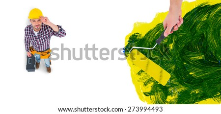 Handyman holding paint roller against blue and yellow paint making green - stock photo