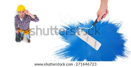 Handyman holding paint roller against blue paint - stock photo